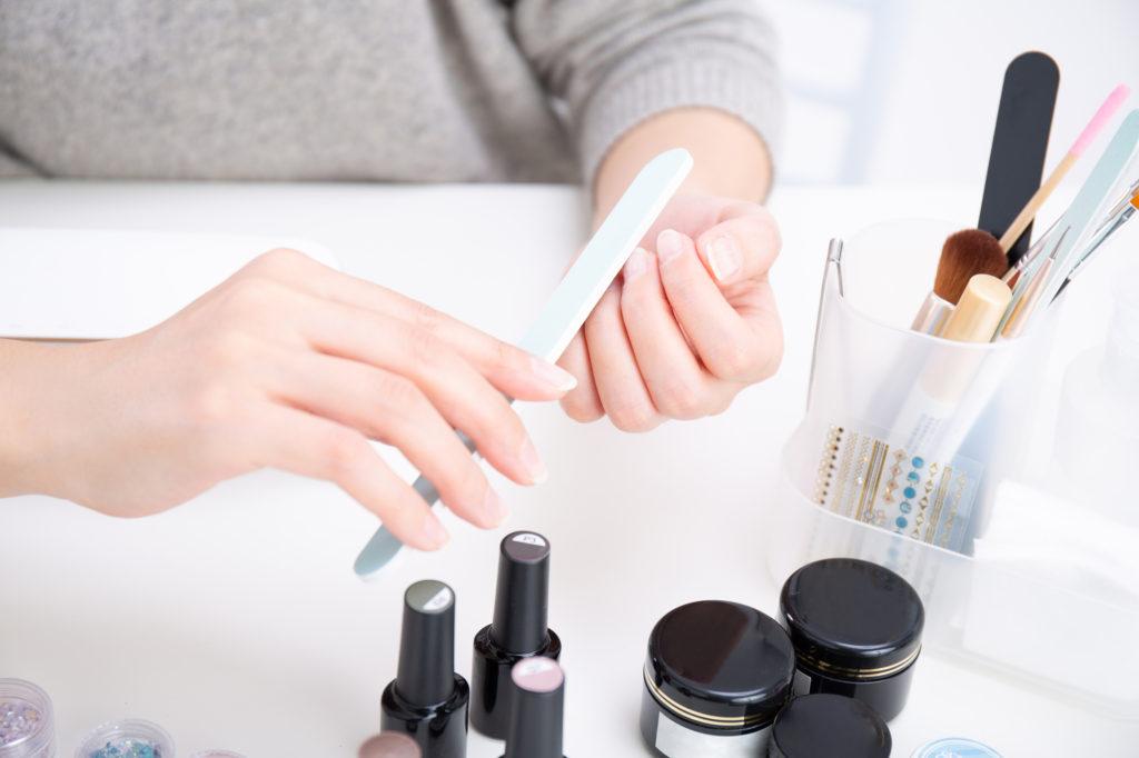 やすりで爪を磨く女性