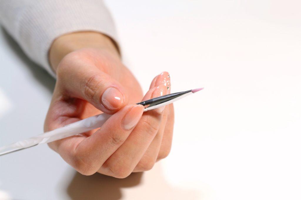 手に筆を持つ女性