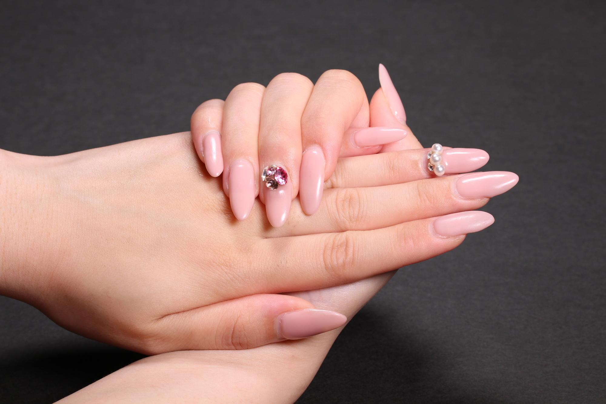 ネイルパーツの付いたピンクのワンカラーネイル