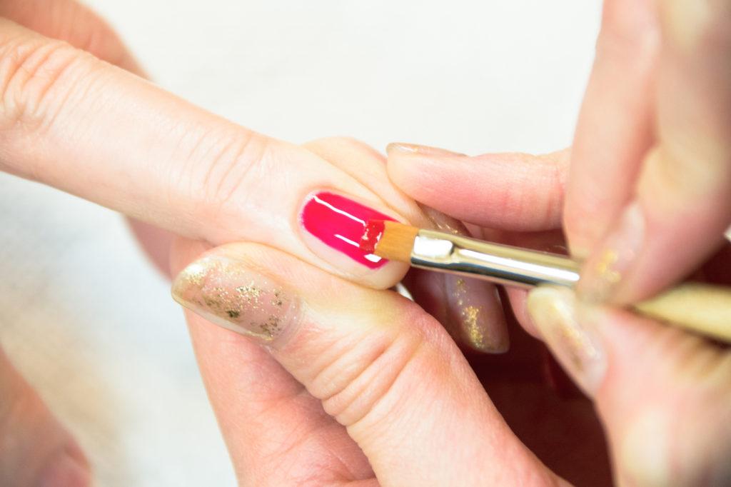 筆で濃いピンクのジェルを塗る