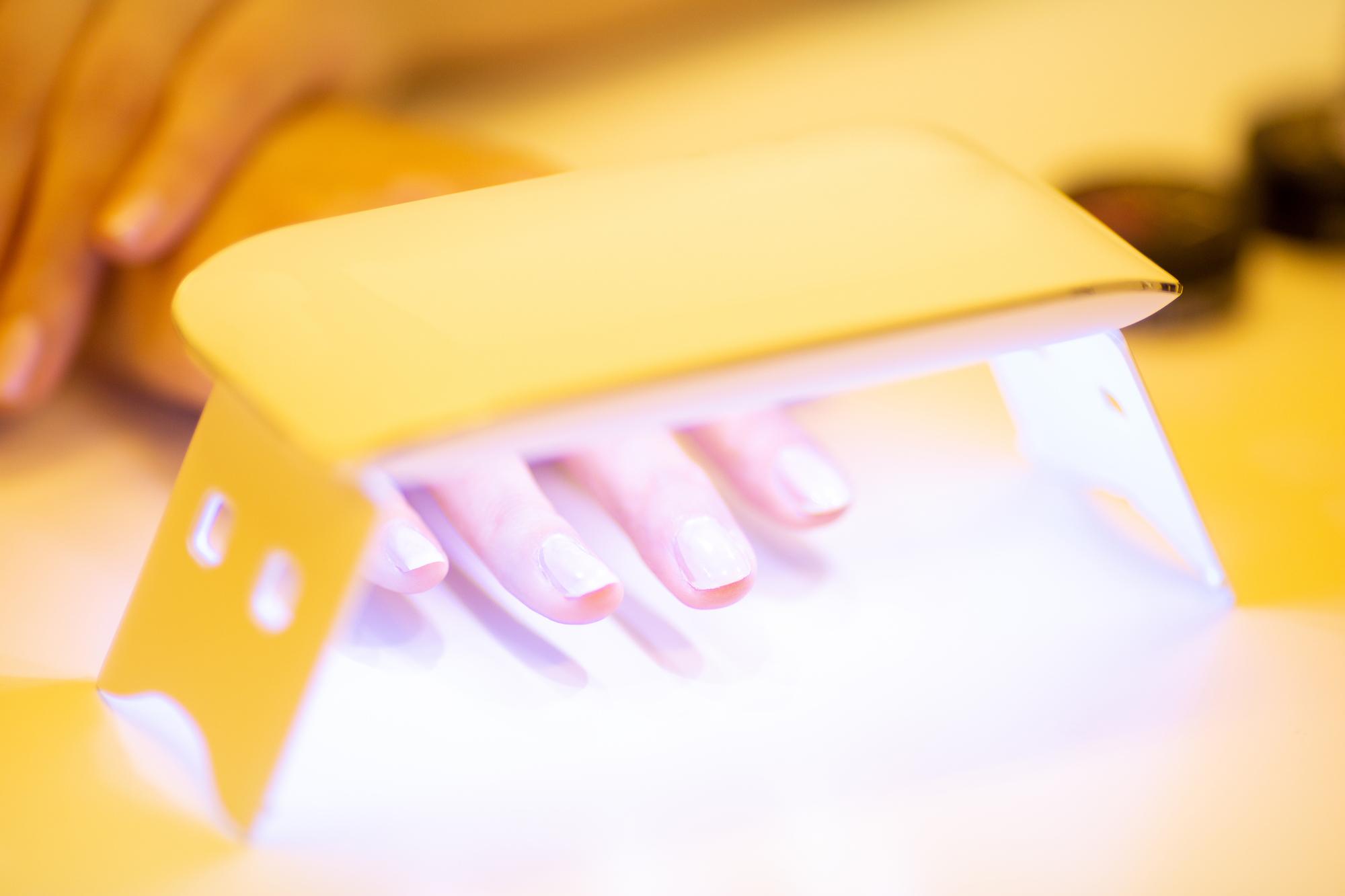 硬化ライトを当ててジェルを固めている女性