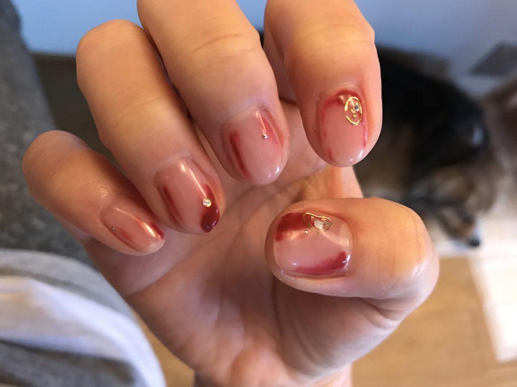 爪の周りを紅い色で装飾しているジェルネイル