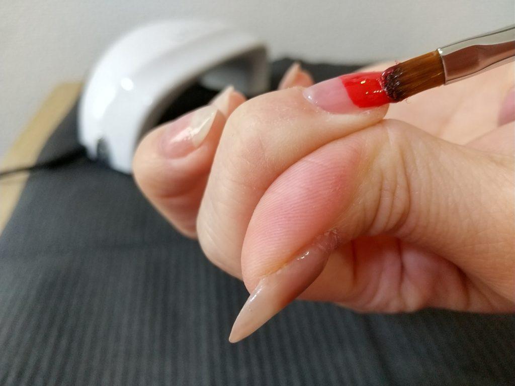 カラージェル工程-爪先の半分を赤いカラージェルで塗布