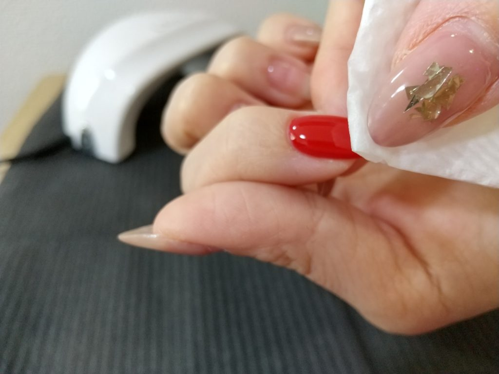 トップジェルとネイルパーツ工程-ワイプで余分なジェルを除去する(爪先)