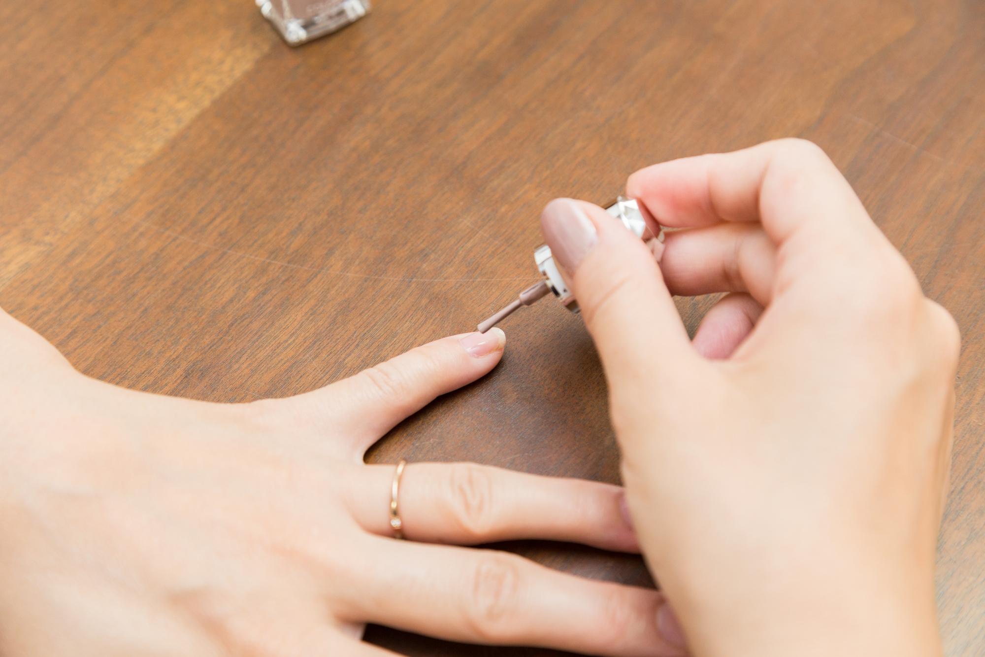 爪にコートを塗る女性